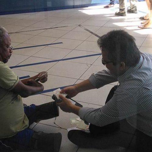 Bom exemplo: Gerente de banco senta no chão para atender cliente com deficiência